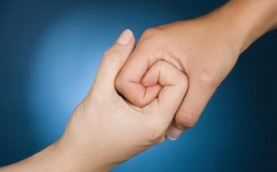 Two hands interlocked to suggest collective strength