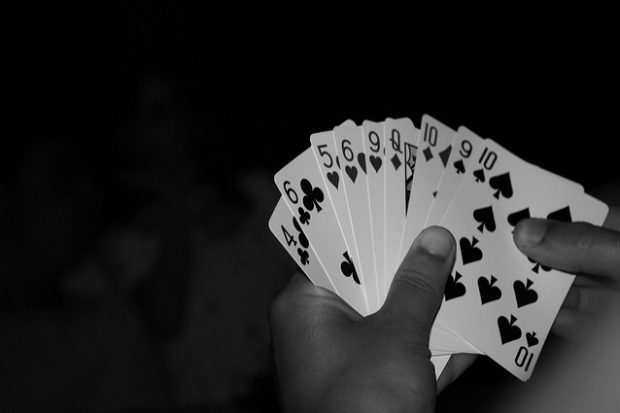 A hand of playing cards fanned out against a black background