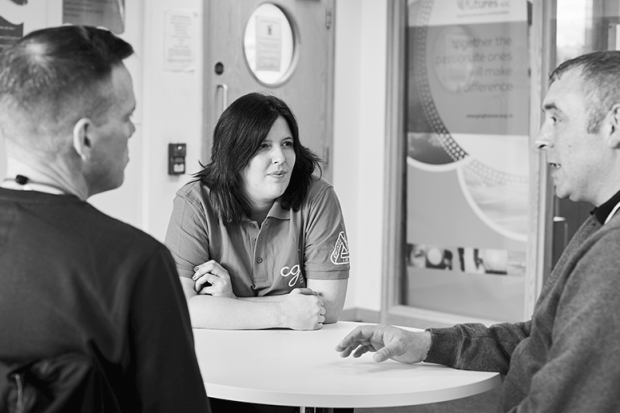 A Change Grow Live colleague in conversation with two service users in a meeting room