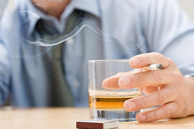 Man holding tumbler of whisky and balancing a cigarette between his fingers