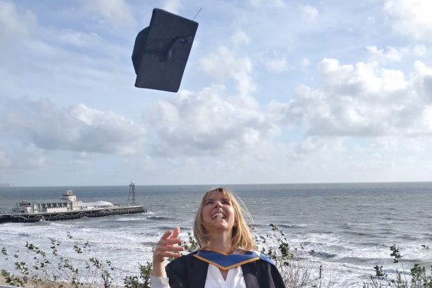 Nicola Shawyer on her graduation day, throwimg her mortar board high in the air and smiling
