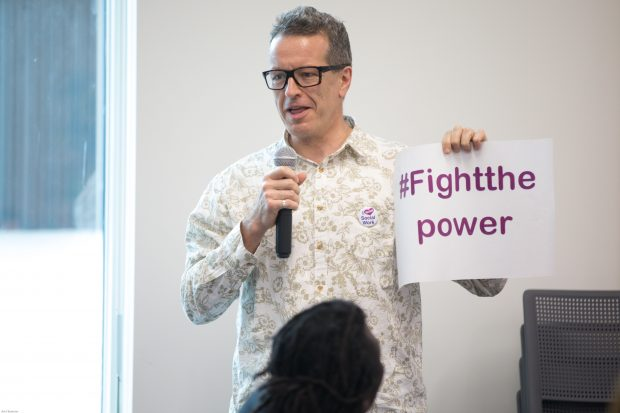 A man holds up a sign with the words fight the power on it as part of steering group discussions