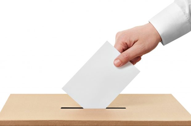 ballot box - hand posting vote in slot