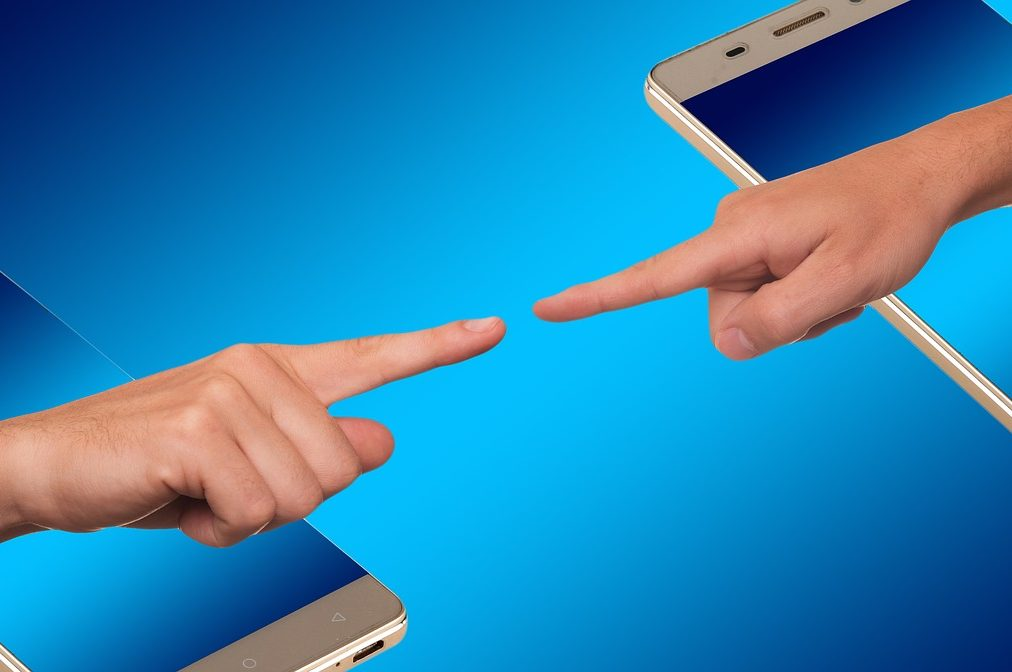 two hands reaching out of smartphones towards each other