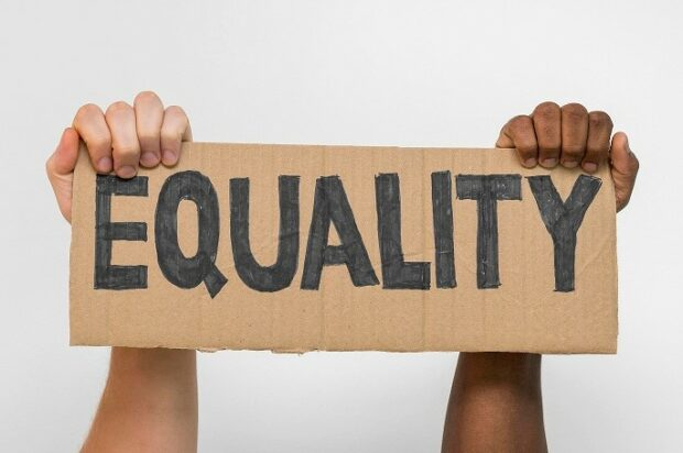 Black and white hands holding up a sign with the word 'equality'.